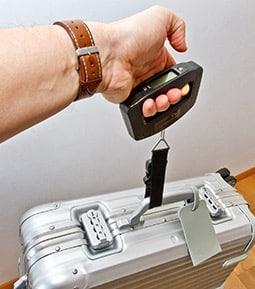 Eine Kofferwaage am Gewicht austesten